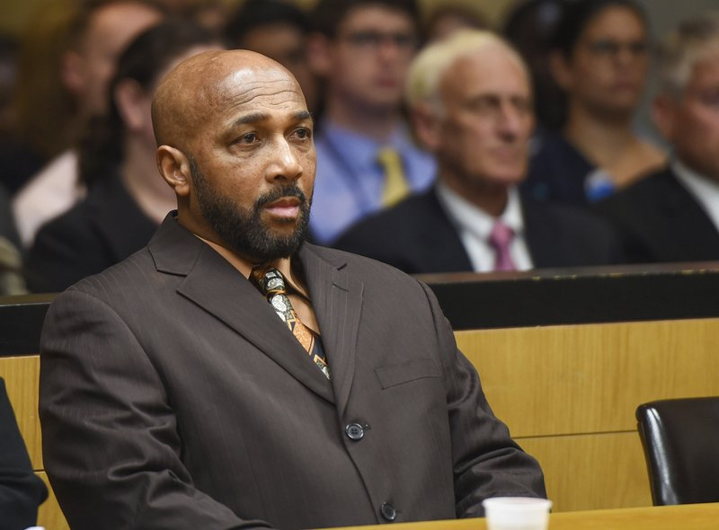Keith Bush sits at the defense table during a hearing at Suffolk County Courthouse in Riverhead, N.Y., to have his 1975 murder conviction vacated, Wednesday, May 22, 2019. Bush, who spent 33 years in prison for murdering a high school classmate, had his conviction overturned Wednesday after a case review found Long Island prosecutors had long hid the fact that police looked at another possible suspect. (James Carbone/Newsday via AP, Pool)