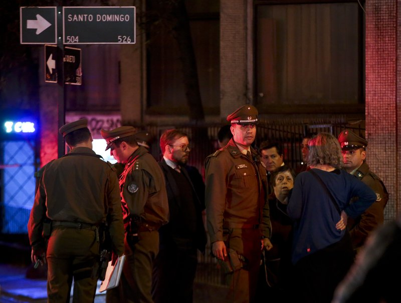 Chilean police talk with neighbors in front a building where six Brazilians died of apparent carbon monoxide poisoning at an old apartment in Santiago, Chile, Wednesday, May 22, 2019. Police commander Rodrigo Soto said officers found four adults and two children dead at the six-story building Wednesday. The fire department said a high concentration of carbon monoxide was measured in the apartment, which it said was completely closed. (AP Photo/Esteban Felix)
