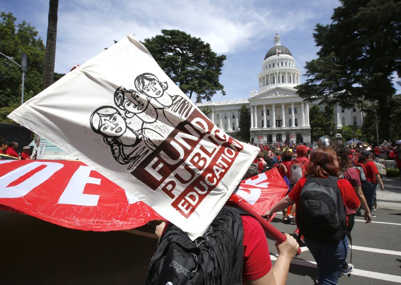 Members of the California Teachers Association and supporters of public education marched to the Capitol as part of RedForEd Day of Action Wednesday, May 22, 2019, in Sacramento, Calif. The marchers were calling on lawmakers to increase funding for public schools. On Wednesday, the state assembly narrowly passed a bill backed by teachers unions to change how charter schools are approved. (AP Photo/Rich Pedroncelli)