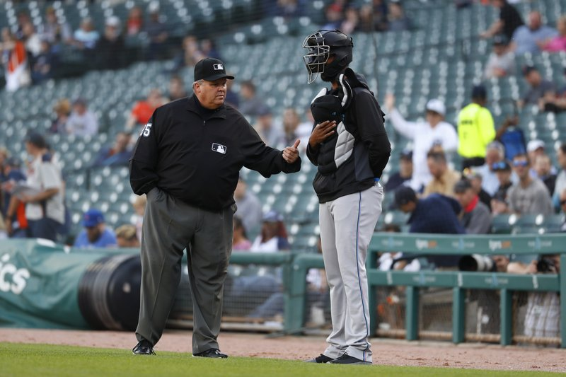 First base umpire D.J. Rayburn tells Miami Marlins pitcher Sandy Alcantara to leave the field before the first pitch of the team's baseball game against the Detroit Tigers in Detroit, Wednesday, May 22, 2019. Alcantara stood with equipment on after national anthem until he was asked to leave the field. (AP Photo/Paul Sancya)