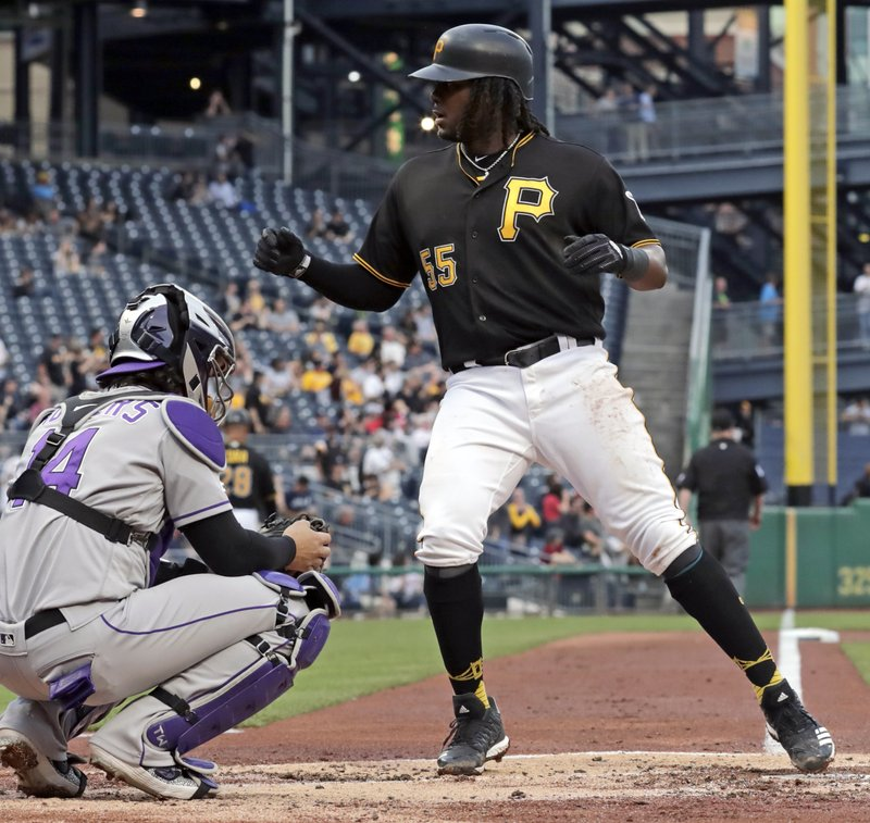 Pittsburgh Pirates' Josh Bell (55) crosses home plate in front of Colorado Rockies catcher Tony Wolters after hitting a solo home run off Rockies starting pitcher Jon Gray during the second inning of a baseball game in Pittsburgh, Wednesday, May 22, 2019. (AP Photo/Gene J. Puskar)