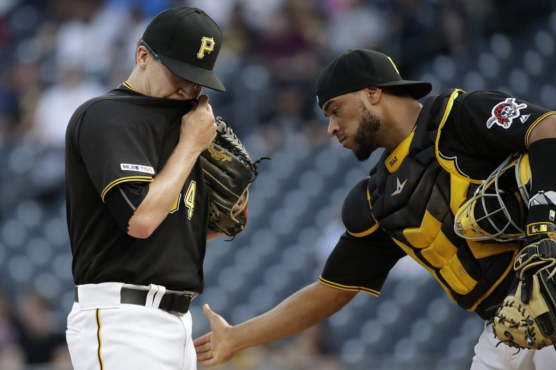 Pittsburgh Pirates starting pitcher Montana DuRapau, left, waits with catcher Elias Diaz, before Diaz turned the ball over to manager Clint Hurdle after giving up a three-run home run to Colorado Rockies' Daniel Murphy during the first inning of a baseball game in Pittsburgh, Wednesday, May 22, 2019. (AP Photo/Gene J. Puskar)