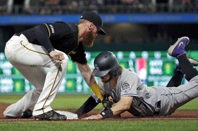 Pittsburgh Pirates third baseman Colin Moran tags out Colorado Rockies' Brendan Rodgers after taking the pickoff throw from catcher Elias Diaz during the fifth inning of a baseball game in Pittsburgh, Wednesday, May 22, 2019. (AP Photo/Gene J. Puskar)