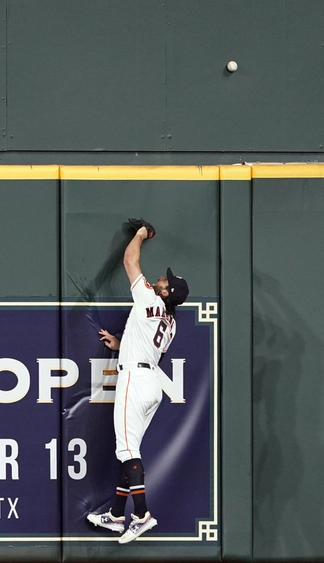 Houston Astros center fielder Jake Marisnick leaps at the wall while trying to catch a home run by Chicago White Sox's Eloy Jimenez during the second inning of a baseball game Wednesday, May 22, 2019, in Houston. (AP Photo/David J. Phillip)