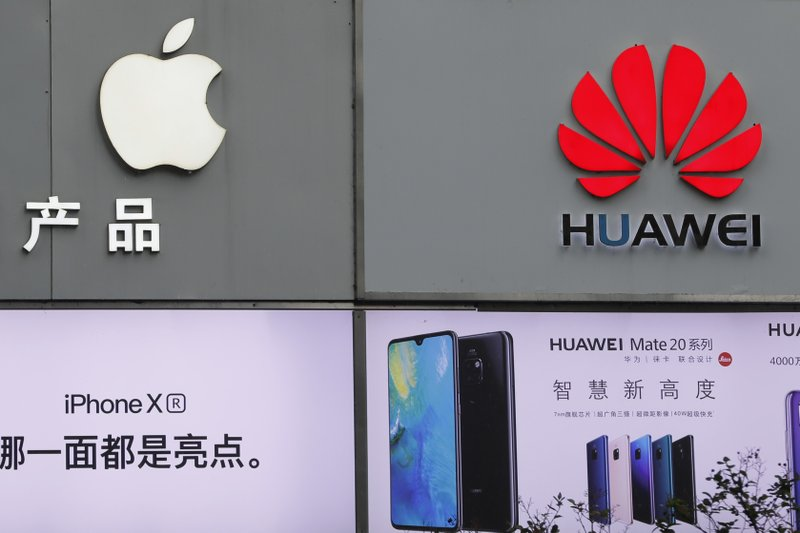 FILE - In this Thursday, March 7, 2019, file photo, logos of Apple and Huawei are displayed outside a mobile phone retail shop in Shenzhen, China's Guangdong province. Few U.S. companies are more vulnerable to a trade war with China than Apple. The Trump administration's decision to bar U.S. technology sales to Huawei, one of China's leading brands, might put Apple in the crosshairs. (AP Photo/Kin Cheung, File)