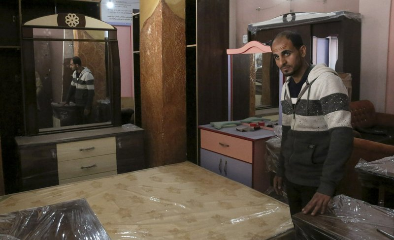 In this April 21, 2019 photo, Palestinian groom Yehiya Taleb, chooses his wedding furniture before his wedding, at a furniture workshop in Gaza City. Hundreds of young men in the Gaza Strip have turned to a small industry of lenders to help them pay for their weddings. Taleb got a job working as a waiter at a cafe earning about $180 a month, but that amount was not enough to cover wedding expenses so he took out a $2,000 package through the Farha Project, one of the wedding financing companies. (AP Photo/Adel Hana)