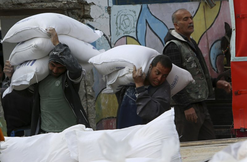 In this April 20, 2019 photo, Palestinian refugees carry sacks of flour distributed by the United Nations Relief and Works Agency, at Shati refugee camp in Gaza City. The blockade Israel and Egypt imposed on Gaza after the Hamas militant group took power in 2007 has ravaged the economy. The skyrocketing unemployment rates, combined with foreign aid cuts and Hamas' mismanagement, has left thousands of families dependent on food aid and social welfare. Many young Gazans have been forced to put off their dreams of marriage because they cannot afford it. (AP Photo/Adel Hana)