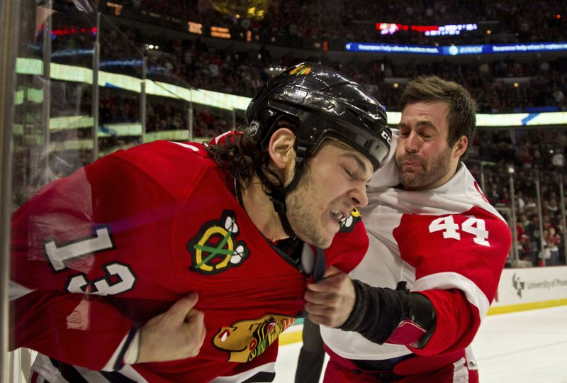 FILE - In this Dec. 30, 2011, file photo, Chicago Blackhawks' Daniel Carcillo and Detroit Red Wings' Todd Bertuzzi fight during the first period of an NHL hockey game in Chicago. The league this fall settled a lawsuit for $18.9 million with more than 300 retired players that included $22,000 each, provisions for testing but no acknowledgement of liability for the players' claims that it failed to protect them from head injuries or warn them of the risks involved with playing. Commissioner Gary Bettman has steadfastly denied a conclusive link between repeated blows to the head and the degenerative brain disease chronic traumatic encephalopathy.  (AP Photo/Charles Cherney, File)
