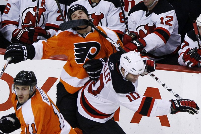 FILE - In this Jan. 8, 2011, file photo, Philadelphia Flyers' Daniel Carcillo, top, is hit in the face by a stick from New Jersey Devils' Rod Pelley during the third period of an NHL hockey game, in Philadelphia. Carcillo is hurting inside and out after seven documented concussions in the National Hockey League and what he believes could be hundreds of traumatic brain injuries. He doesn't remember any of his first five concussions but can't escape the anxiety, depression, lack of impulse control and suicidal thoughts now. (AP Photo/Matt Slocum, File)