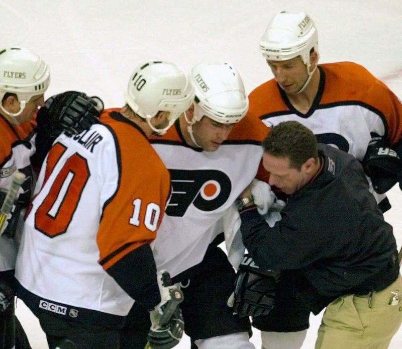 FILE - In this May 26, 2000, file photo, Philadelphia Flyers Eric Lindros, third from right, is assisted after getting hit in the first period of Game 7 of their NHL hockey Eastern Conference finals against the New Jersey Devils in Philadelphia. Lindros could easily be the poster boy for concussions in the NHL given his experience.  (AP Photo/Chris Gardner, File)