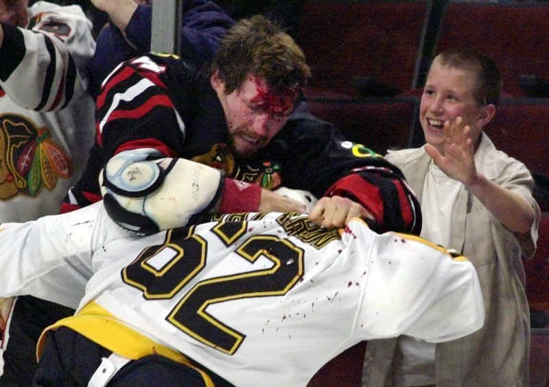 FILE - In this Oct. 28, 2001, file photo, Chicago Blackhawks' Bob Probert, left, and Boston Bruins' Andrei Nazarov (62), of Russia, mix it up along the boards during a first period fight in Chicago. Steve Montador, Todd Ewen, Wade Belak, Rick Rypien, Bob Probert, Jeff Parker Derek Boogaard are dead. Many of them were enforcers tasked with delivering and taking punches for teammates and all took many blows to the head (AP Photo/Fred Jewell, File)