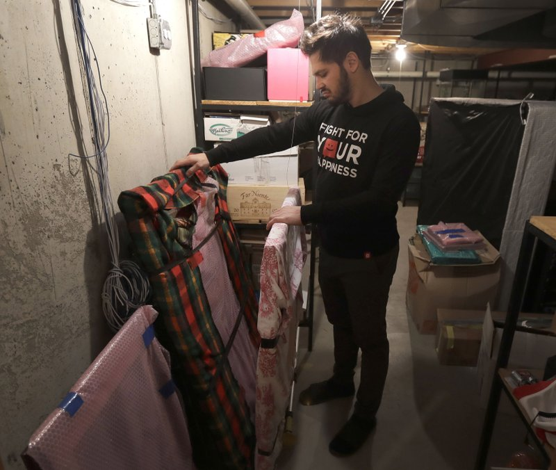 In this Tuesday, April 2, 2019, photo, former NHL player Dan Carcillo looks through some of his memorabilia that is still wrapped that his grandfather collected in the basement of Carcillo's rural home in Homer Glen, Ill. Carcillo, 34, hung up his skates in 2015 and wants to be known as Daniel Carcillo who used to play hockey, not Daniel Carcillo the hockey player. He spends his days now trying to manage the damage the sport did to him while also crusading against the concussion epidemic in the NHL that has been reduced but not eliminated and remains a crucial issue as the Stanley Cup Final opens Monday. (AP Photo/Charles Rex Arbogast)