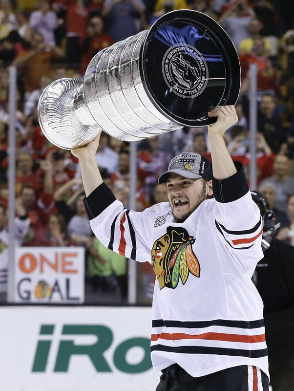 FILE - In this June 24, 2013, file photo, Chicago Blackhawks left wing Daniel Carcillo hoists the Stanley Cup after the Blackhawks beat the Boston Bruins 3-2 in Game 6 of the NHL hockey Stanley Cup Finals in Boston. Carcillo sometimes gets angry talking about his situation, how he feels like generations of players were lied to about what's happening to their brains. Carcillo doesn't have a full-time job and estimates he has two years until he goes bankrupt. That's why he considers selling his two Stanley Cup rings to pay for treatment and support his family because he estimates he has two years until he goes bankrupt. (AP Photo/Elise Amendola, File)