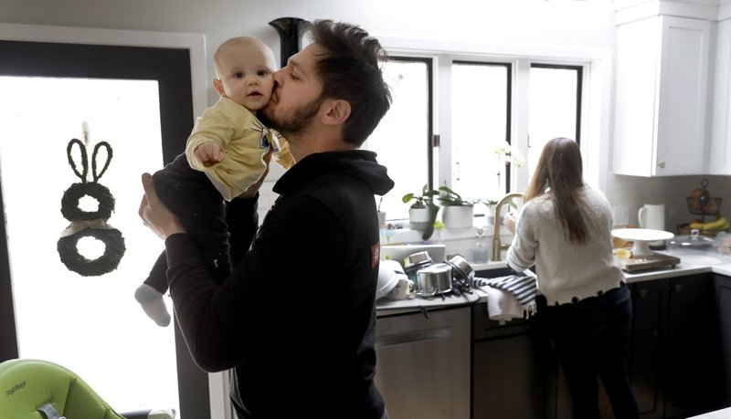 In this Tuesday, April 2, 2019, photo, former NHL player Dan Carcillo kisses his daughter Scarlett as his wife Ela works in the kitchen at their rural home in Homer Glen, Ill. Carcillo is hurting inside and out after seven documented concussions in the National Hockey League and what he believes could be hundreds of traumatic brain injuries.