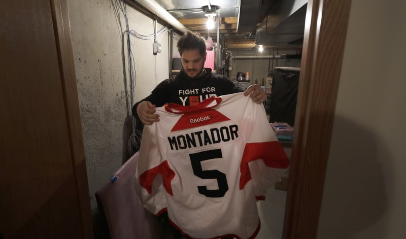 In this Tuesday, April 2, 2019, photo, former NHL player Dan Carcillo looks at the hockey sweater of his friend Steve Montador in the basement of his rural home in Homer Glen, Ill. Montador is one of five players posthumously diagnosed with the brain disease known as Chronic traumatic encephalopathy. Montador's 2015 death hit Carcillo hard because he saw his close friend struggle for so long even after seeking help. Christmas, New Year's and the months of January and February are still a struggle. (AP Photo/Charles Rex Arbogast)