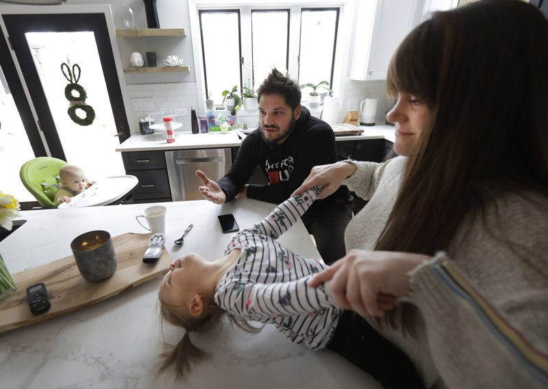 In this Tuesday, April 2, 2019, photo, former NHL player Dan Carcillo responds to a question during an interview with The Associated Press, as his wife Ela, right, and daughters, Laila, center and Scarlett, hang out in the kitchen at their rural home in Homer Glen, Ill. This is the family he always wanted, just not the life he expected. Carcillo is hurting inside and out after seven documented concussions in the National Hockey League and what he believes could be hundreds of traumatic brain injuries. Almost a year since his last round of neurological treatment in early April, the bad days outnumber the good and darkness has returned.  (AP Photo/Charles Rex Arbogast)