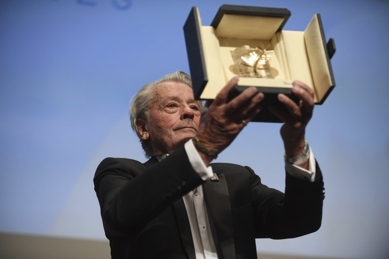 French actor Alain Delon holds his honorary Palme D'Or award during the Cannes Film Festival on May 19. (Photo by Arthur Mola/Invision/AP)