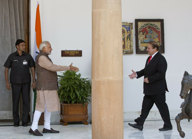 """FILE - In this May 27, 2014 file photo, Indian Prime Minister Narendra Modi, left, walks to shake hand with his Pakistani counterpart Nawaz Sharif before the start of their meeting in New Delhi, India. Indian Prime Minister Narendra Modi's party claimed it had won re-election with a commanding lead in vote count Thursday, May 23, 2019. When India retaliated after a suicide bombing in Kashmir with an airstrike of an alleged militant training camp inside Pakistan, Modi started referring to himself as India's """"chowkidar,"""" or watchman, adding it as a prefix to his official Twitter account. Party leaders and a number of his 47.3 million Twitter followers quickly followed suit. (AP Photo/Manish Swarup, File)"""