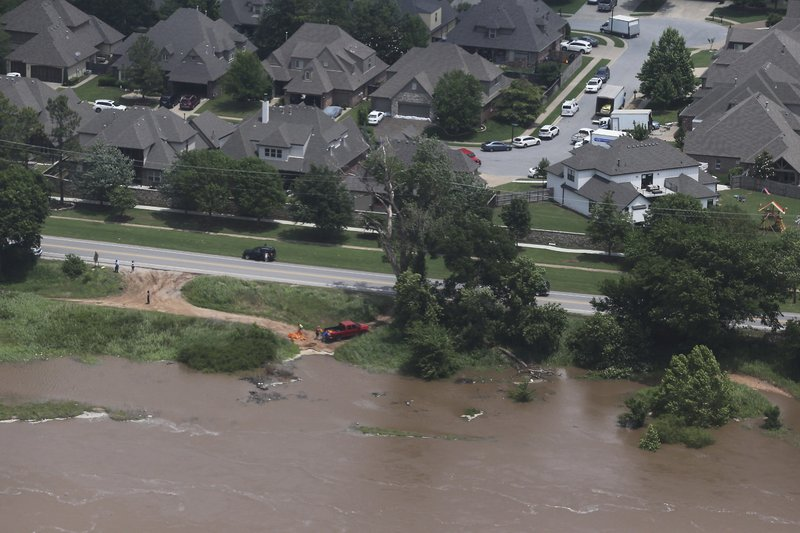 Flood water encroach homes near 118th and Delaware on the Arkansas river on Wednesday, May 22, 2019. Authorities on Wednesday encouraged people living along the Arkansas River in the Tulsa suburb of Bixby and low-lying areas near creeks both north and south of Okmulgee, about 35 miles (56 kilometers) south of Tulsa. to leave their homes. (Tom Gilbert/Tulsa World via AP)