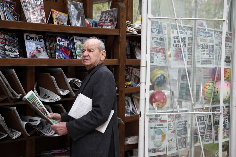 In this Tuesday, May 14, 2019, photo an elderly woman holds a sport newspaper in Karpenisi town at Evrytania region, in central Greece. As balloting for the European Parliament gets underway Thursday and continues through Sunday voters over 55 are emerging as a powerful bloc on a rapidly aging continent as younger voters stay away from the polls in growing numbers. (AP Photo/Thanassis Stavrakis)