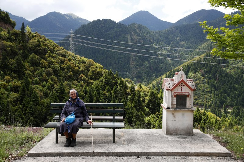 In this Wednesday, May 15, 2019, photo Alexandra Triantafyllopoulou, 91, sits on a bench in the village of Kalesmeno at Evrytania region, in central Greece. As balloting for the European Parliament gets underway Thursday and continues through Sunday voters over 55 are emerging as a powerful bloc on a rapidly aging continent as younger voters stay away from the polls in growing numbers. (AP Photo/Thanassis Stavrakis)