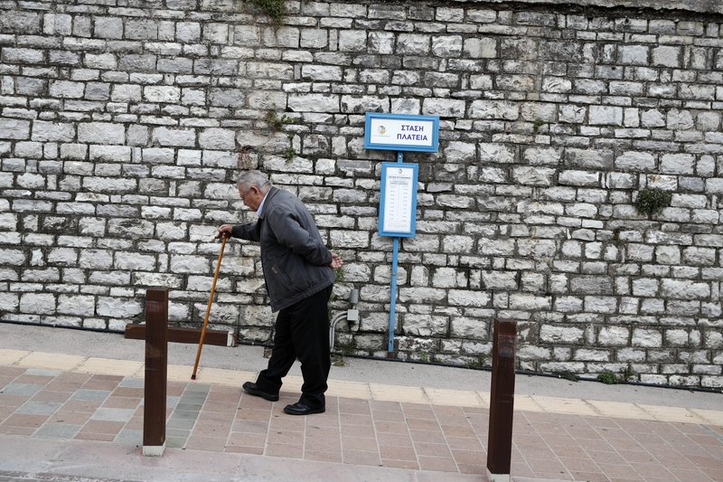 In this Tuesday, May 14, 2019, photo an elderly man walks uphill in Karpenisi town, at Evrytania region, in central Greece. The area, a winding, three-hour drive from Athens, has the oldest population in the whole European Union, 54.3 on average. (AP Photo/Thanassis Stavrakis)