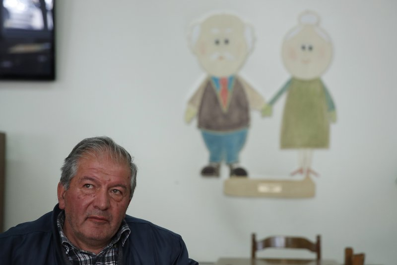 In this Tuesday, May 14, 2019, photo Vassilios Ragios retired carpenter, 63, sits at a community center for the retired in Karpenisi town at Evrytania region, in central Greece. The area, a winding, three-hour drive from Athens, has the oldest population in the whole European Union, 54.3 on average. (AP Photo/Thanassis Stavrakis)