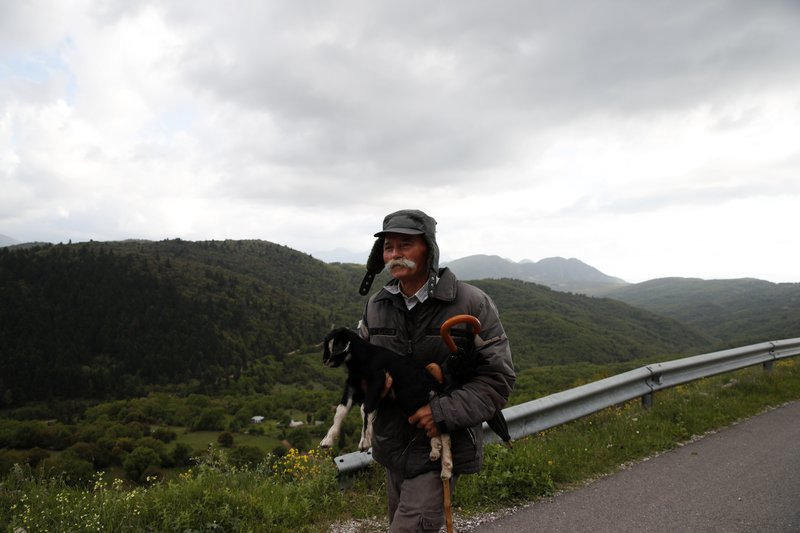 In this Tuesday, May 14, 2019, photo an elderly man holds a goat kid in Kerasohori village at Evrytania region, in central Greece. The area, a winding, three-hour drive from Athens, has the oldest population in the whole European Union, 54.3 on average. (AP Photo/Thanassis Stavrakis)