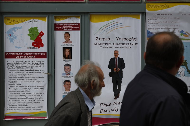 In this Tuesday, May 14, 2019, photo an elderly man passes election posters in Karpenisi town at Evrytania region, in central Greece. As balloting for the European Parliament gets underway Thursday and continues through Sunday voters over 55 are emerging as a powerful bloc on a rapidly aging continent as younger voters stay away from the polls in growing numbers. (AP Photo/Thanassis Stavrakis)