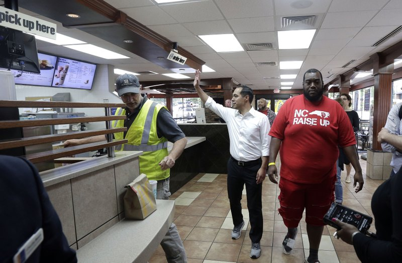 Presidential candidate and former U.S. Department of Housing and Urban Development Julian Castro waves to employees inside of a McDonald's during a rally with employees and other activists demanding fairer pay, better working conditions, and the right to unionize in Durham, N.C., Thursday, May 23, 2019. (AP Photo/Gerry Broome)