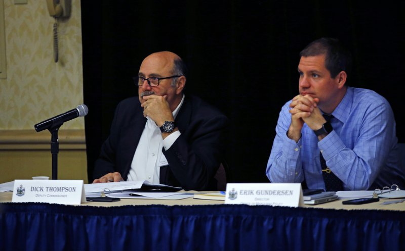 Dick Thompson, left, and Erik Gundersen of the Maine Office of Marijuana Policy, listen to testimony at a hearing, Thursday, May 23, 2109, in Portland, Maine. Many used the event to implore the state to protect the small businesses and growers in the state's cannabis industry. State officials are working to pass a legal framework before marijuana could be sold in stores. (AP Photo/Robert F. Bukaty)