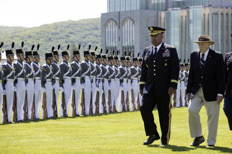 In this May 22, 2019 photo, West Point Superintendent Lt. Gen. Darryl Williams, second from right, attends Parade Day at the U.S. Military Academy in West Point, N.Y. Walking with him is Don Carter, 94, from the class of 1944. West Point remains mostly white and mostly male. (AP Photo/Mark Lennihan)