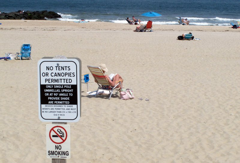 In this Monday, May 20, 2019 photo, beachgoers sit on the sand beyond a sign indicating that smoking is prohibited on the beach in Spring Lake, N.J. A statewide smoking ban is in effect at New Jersey's beaches for the start of the 2019 summer season, although towns can set aside up to 15% as smoking sections. (AP Photo/Wayne Parry)