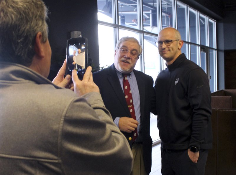 University of Connecticut NCAA college basketball coach Dan Hurley, right, poses for a photo with fan Bruce Fox on Thursday, May 23, 2019, at Dunkin' Donuts Park in Hartford, Conn. Hurley and other UConn coaches are touring the state as part of the second annual Coaches Road Show to engage the school's fan base. (AP Photo/Pat Eaton-Robb)