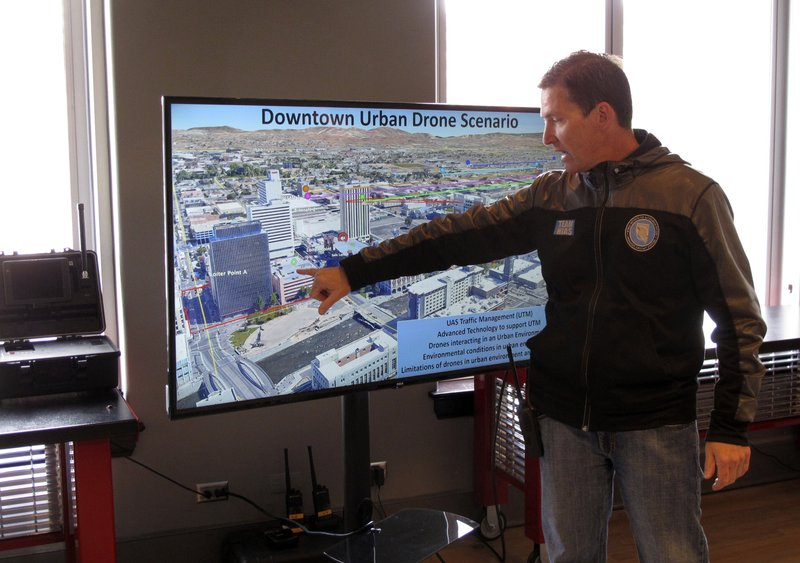 In this Tuesday, May 21, 2019 photo, Chris Walach, executive director of the Nevada Institute of Autonomous Systems, points to the the launch pad on a casino parking garage in downtown Reno, Nev., where NASA conducted the first drone tests of their kind in an urban setting. A series of simulations are testing the emerging technology that someday will be used to manage travel of hundreds of thousands of commercial, unmanned aerial vehicles (UAVs) delivering packages.  (AP Photo/Scott Sonner)