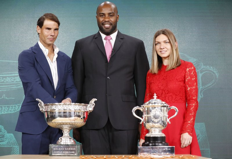 Defending champions Spain's Rafael Nadal, left, French judoka Teddy Riner, center, and Romania's Simona Halep pose next to the cups during the draw of the French Open tennis tournament at the Roland Garros stadium in Paris, Thursday, May 23, 2019. The French Open tennis tournament starts Sunday May 26. (AP Photo/Michel Euler)