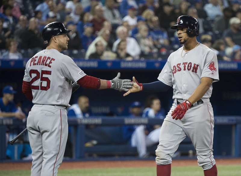 Boston Red Sox's Xander Bogaerts, right, celebrates scoring with teammate Steve Pearce (25) during the sixth inning  of a baseball game in Toronto, Thursday, May 23, 2019. (Nathan Denette/The Canadian Press via AP)