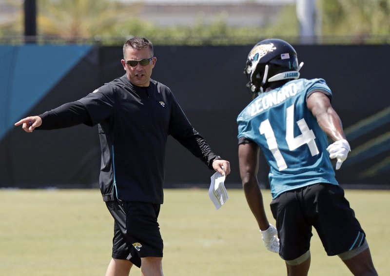 Jacksonville Jaguars offensive coordinator John DeFilippo, left, directs wide receiver Raphael Leonard (14) during an NFL football practice, Tuesday, May 21, 2019, in Jacksonville, Fla. (AP Photo/John Raoux)