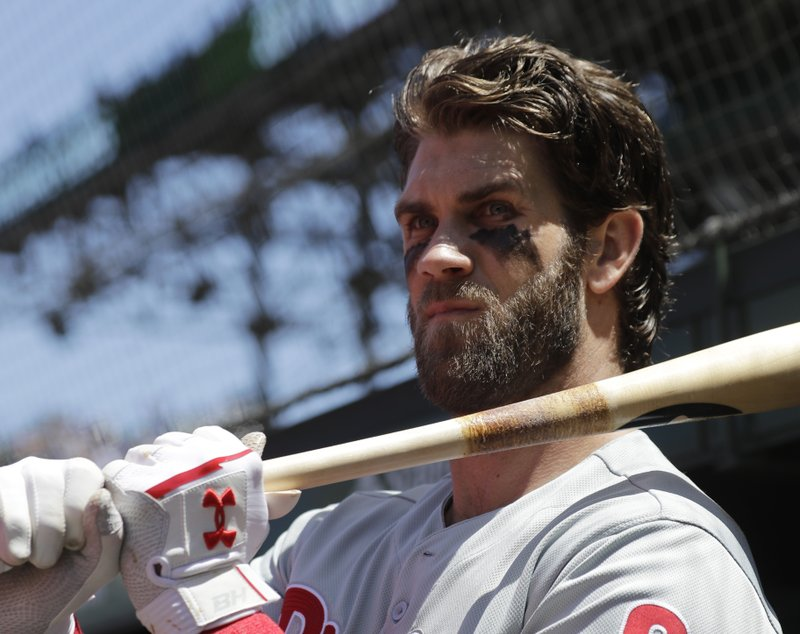 Philadelphia Phillies' Bryce Harper looks to the field from the dugout during the third inning of a baseball game against the Chicago Cubs, Thursday, May 23, 2019, in Chicago. (AP Photo/Nam Y. Huh)