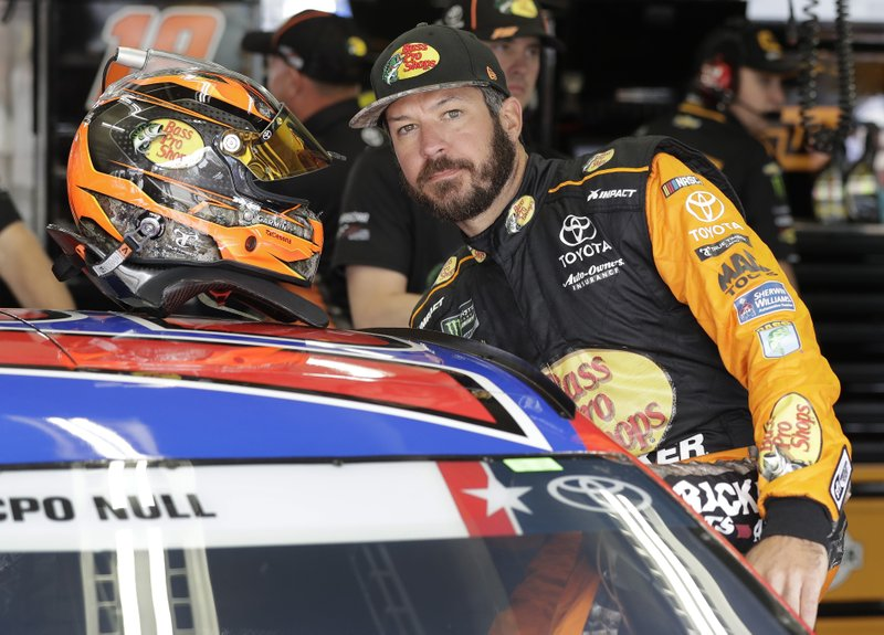 Martin Truex Jr. climbs into his car before practice for Sunday's NASCAR Coca-Cola 600 Cup series auto race at Charlotte Motor Speedway in Concord, N.C., Thursday, May 23, 2019. (AP Photo/Chuck Burton)