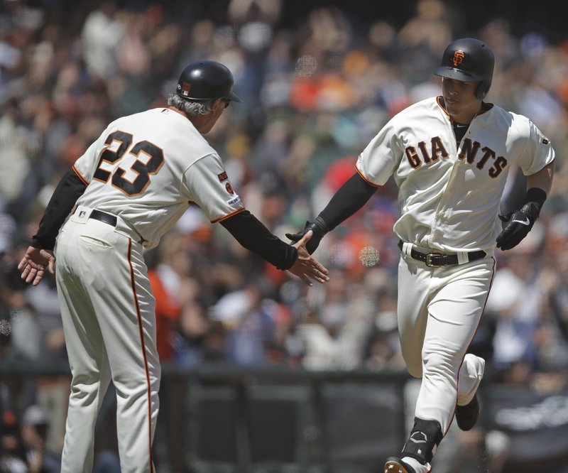 San Francisco Giants' Tyler Austin, right, is congratulated by third base coach Ron Wotus (23) after hitting a home run off Atlanta Braves pitcher Sean Newcomb in the seventh inning of a baseball game Thursday, May 23, 2019, in San Francisco. (AP Photo/Ben Margot)