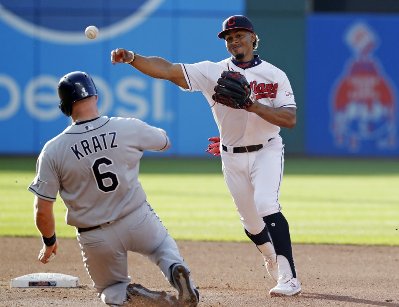 Cleveland Indians' Francisco Lindor, right, throws to first after forcing out Tampa Bay Rays' Erik Kratz at second base during the fourth inning of a baseball game Thursday, May 23, 2019, in Cleveland. Daniel Robertson was out at first base for the double play. (AP Photo/Tony Dejak)