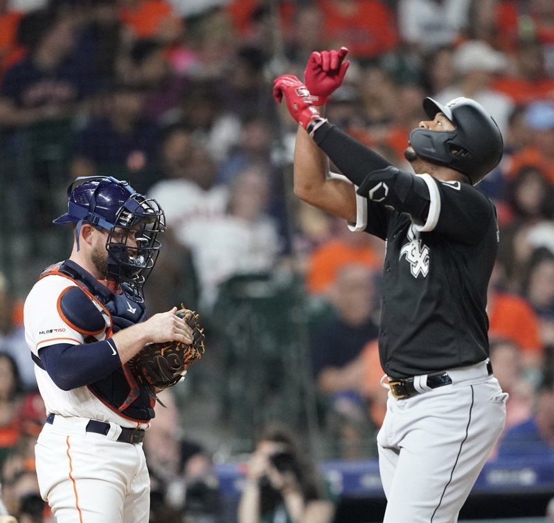 Chicago White Sox's Eloy Jimenez, right, celebrates after hitting a home run as Houston Astros catcher Max Stassi stands at home plate during the fourth inning of a baseball game Thursday, May 23, 2019, in Houston. (AP Photo/David J. Phillip)