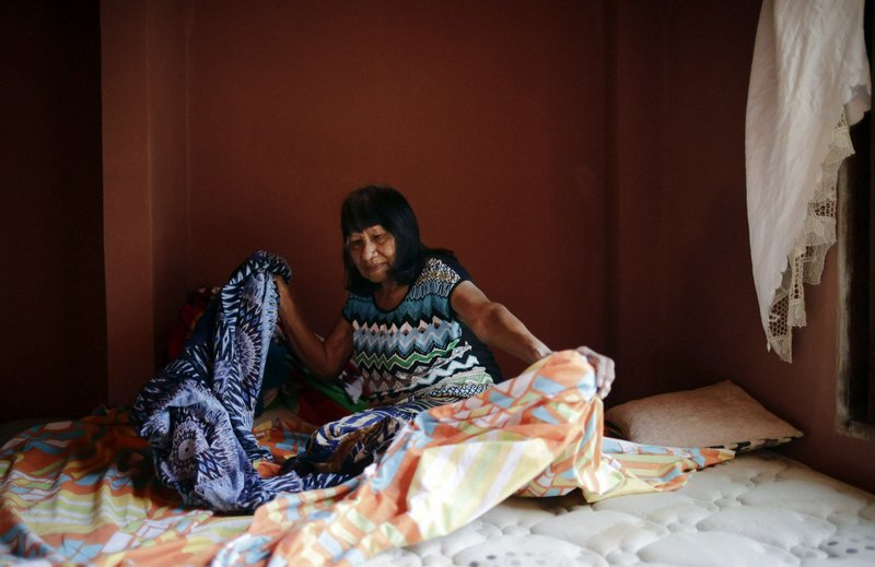 Maka indigenous leader-in-training Tsiweyenki, or Gloria Elizeche in Spanish, makes a bed at her home in Mariano Roque Alonso, Paraguay, Wednesday, April 17. In addition to the standard political tasks as chief, she'll be principal of a primary and secondary school, lead a labor union and soccer team and head the local Baptist church. (AP Photo/Jorge Saenz)
