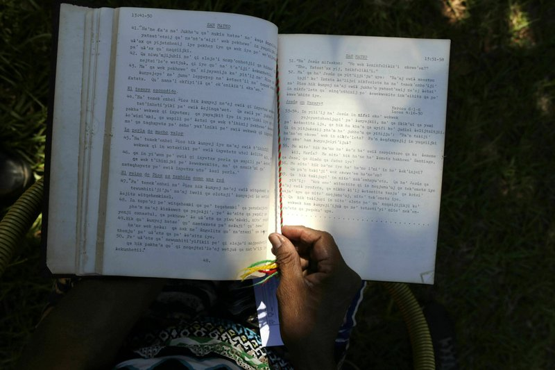 The hands of Maka indigenous leader-in-training Tsiweyenki, or Gloria Elizeche in Spanish, handles a copy of the Bible translated into her native language in Mariano Roque Alonso, Paraguay, Wednesday, April 17, 2019. Tsiweyenki, born in the Chaco, attended a Baptist missionary school where she learned to read and write in the Maka language, into which parts of the Bible have been translated. (AP Photo/Jorge Saenz)