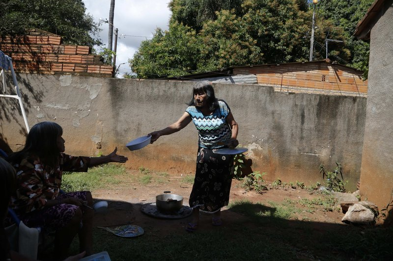 Maka indigenous leader-in-training Tsiweyenki, or Gloria Elizeche in Spanish, passes a plate to her sister Cristina as they cook in her backyard in Mariano Roque Alonso, Paraguay, Monday, April 29, 2019. Tsiweyenki's upcoming position as chief of an entire ethnic group is a landmark for Paraguay where women gained the vote only in 1961 and the country still trails neighboring nations in the number of women in major political posts, according to the U.N. women's agency. (AP Photo/Jorge Saenz)