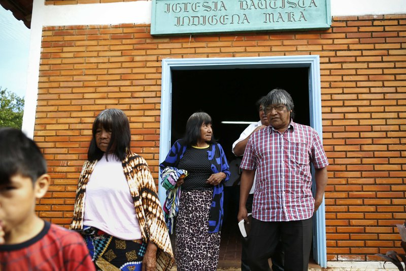 Maka indigenous leader-in-training Tsiweyenki, or Gloria Elizeche in Spanish, center, talks to interim chief Mateo Martinez as they leave a worship service in Mariano Roque Alonso, Paraguay, Sunday, May 5, 2019. Martínez worked as the secretary for late leader Andrés Chemei, Tsiweyenki's husband who died in February. (AP Photo/Jorge Saenz)