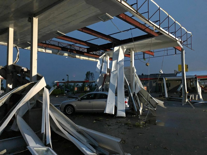 A car is trapped under the fallen metal roof of the Break Time gas station and convenience store in tornado-hit Jefferson City, MO., Thursday, May 23, 2019. The National Weather Service has confirmed a large and destructive tornado has touched down in Missouri's state capital, causing heavy damage and trapping multiple people in the wreckage of their homes. (AP Photo/David A. Lieb)