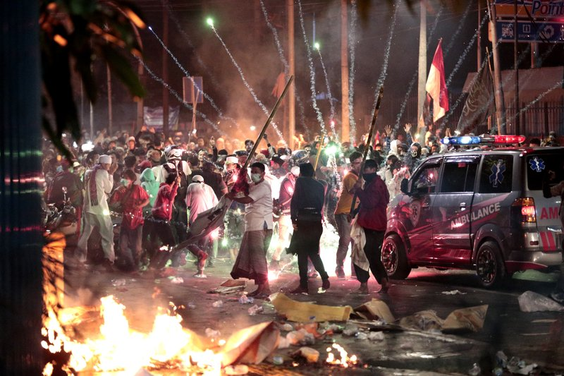 In this Wednesday, May 22, 2019, file photo, firecrackers explode near supporters of presidential candidate Prabowo Subianto during clashes with the police in Jakarta, Indonesia. Indonesian President Joko Widodo said authorities have the volatile situation in the country's capital under control after six people died Wednesday in riots by supporters of his losing rival in last month's presidential election. (AP Photo/Dita Alangkara, File)