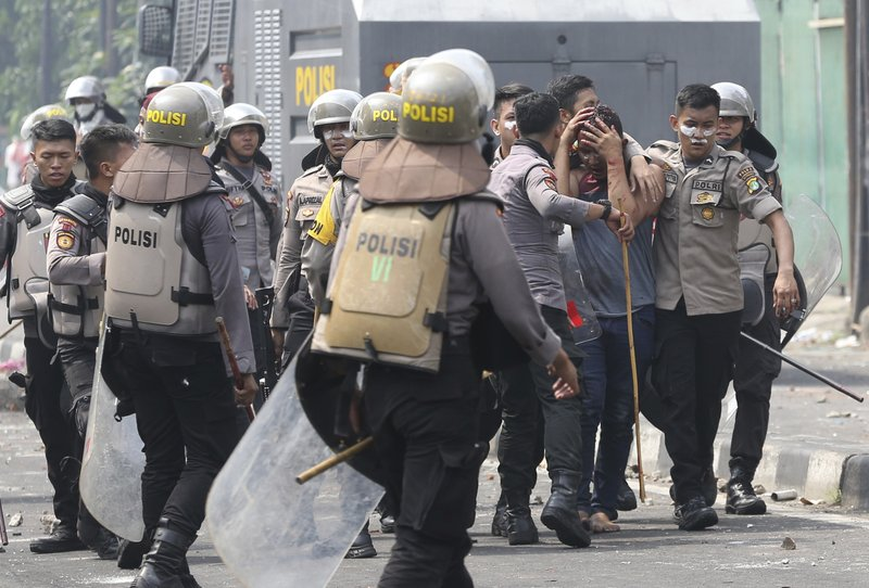 In this Wednesday, May 22, 2019, file photo, Indonesian police arrest a supporter of the losing presidential candidate in Jakarta, Indonesia. Supporters of the losing presidential candidate burned vehicles and battled police and the government announced restrictions on social media. (AP Photo/Achmad Ibrahim, File)